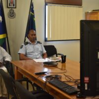 RSIPF Commissioner Mangau (right) with Assistant Commissioner Corporate Support, Ian Bara listening to presentations during the teleconferenc